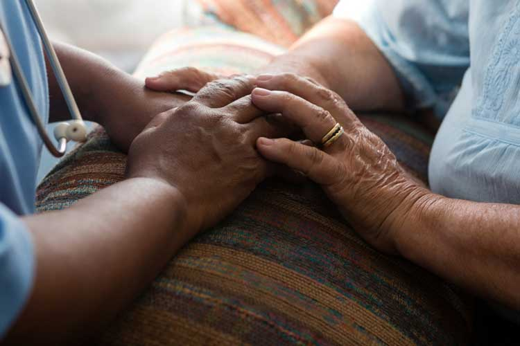 Nurse comforting elderly person | Image