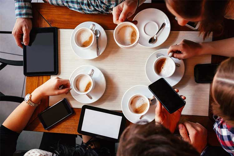 Vertical view of a group gathered drinking coffee and using technology | Image