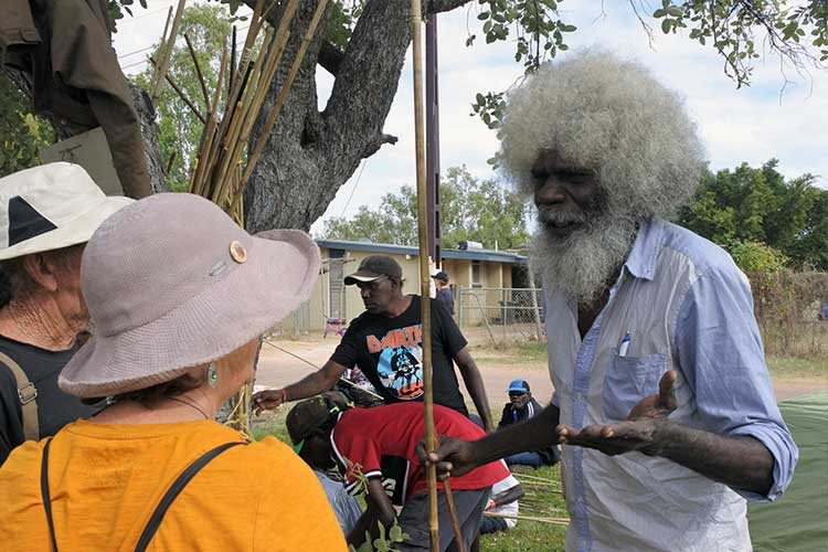 Indigenous Australian talking with non-indigenous Australian | Image