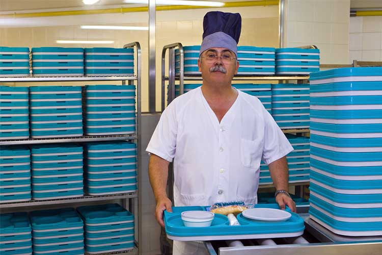 Canteen worker at healthcare facility holding plate tray of food | Image