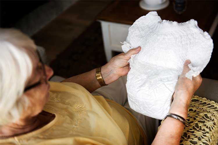Elderly woman holding incontinence product | Image