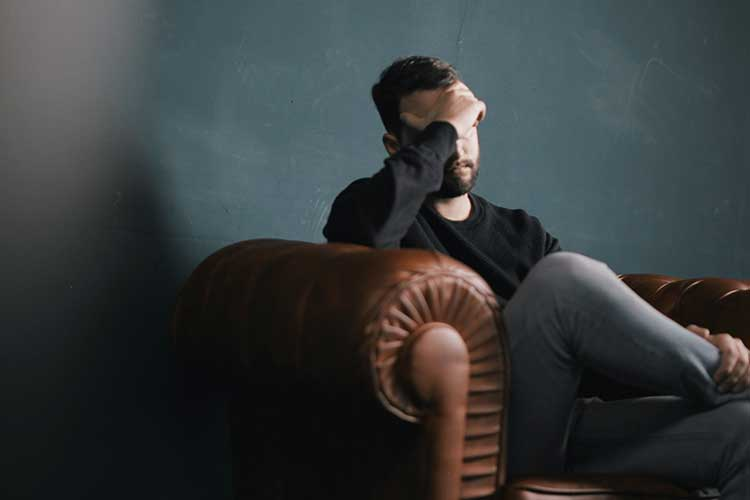 Upset man with hand on head sitting in chair | Image