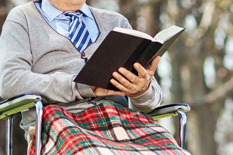 Elderly person reading a book | Image