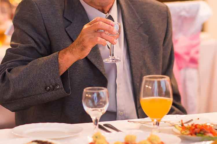 Elderly man sitting at a dining table setting | Image