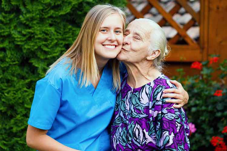 Elderly woman kissing nurse on the cheek | Image