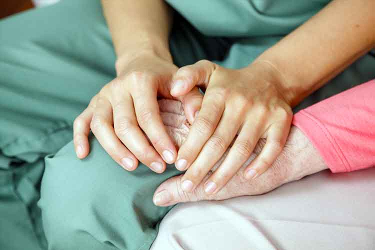 Nurse holding elderly persons hand | Image