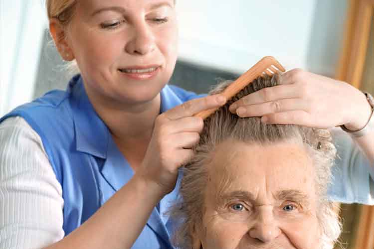Carer brushing elderly womans hair | Image