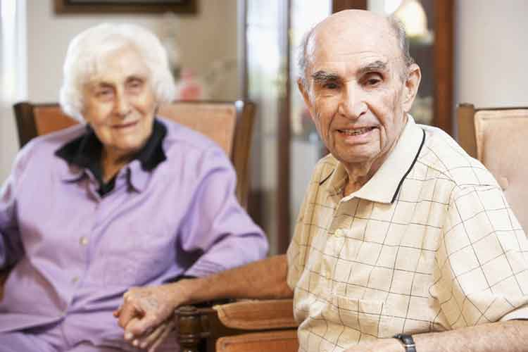 Elderly couple sitting and holding hands | Image