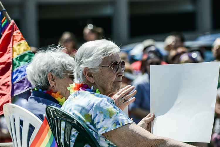 Elderly couple sitting outside holding a sign | Image