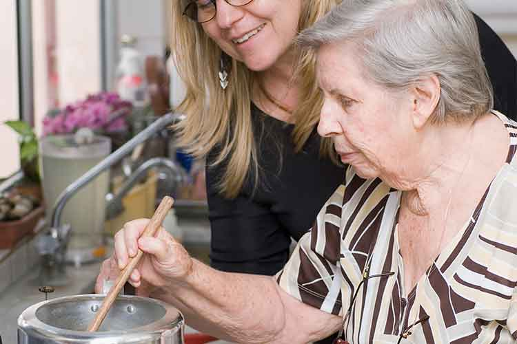 Elderly woman cooking with support of another woman | Image