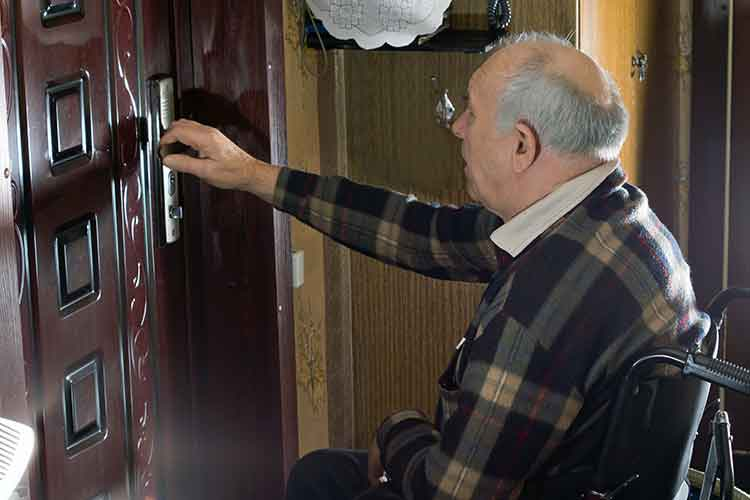 Elderly male in wheelchair opening a door | Image