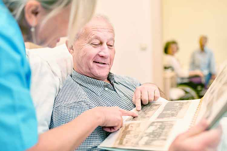 Elderly male reading newspaper with a nurse | Image