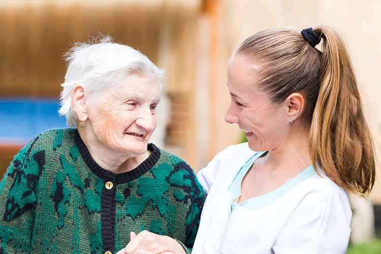 Healthcare worker and elderly woman smiling | Image
