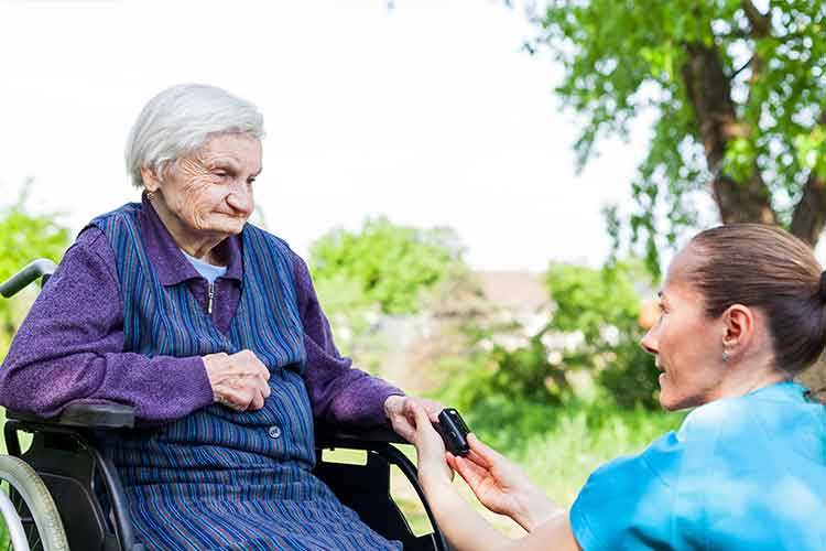 Nurse using a sats probe on elderly woman | Image