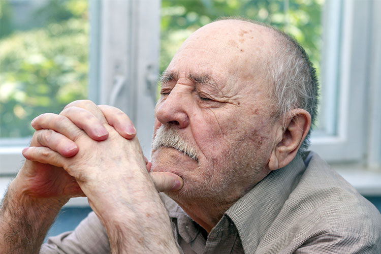 old man with dementia has his eyes closed looking sad
