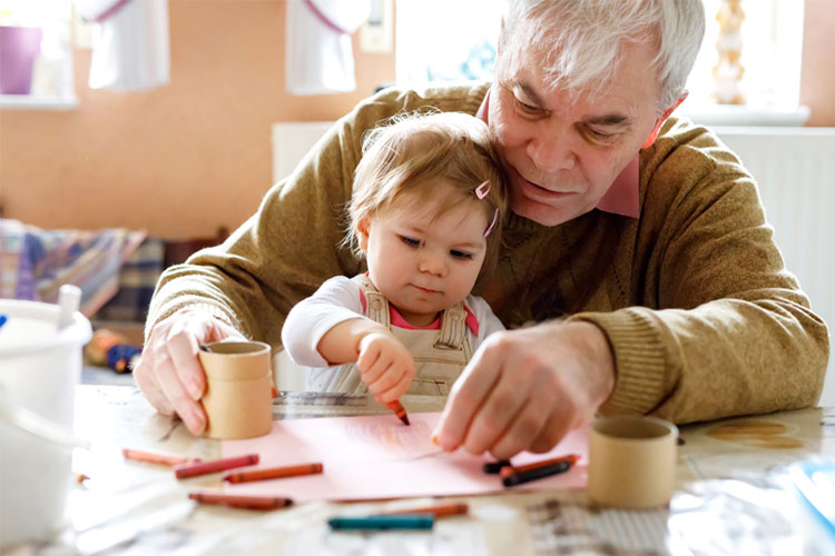 Old man with dementia enjoys doing crafts with granddaughter