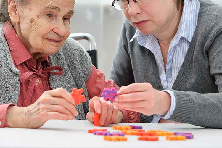 Elderly woman playing with puzzles | Image