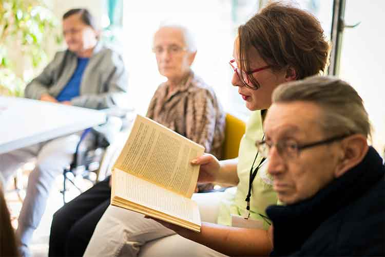 Woman reading a book to elderly people | Image