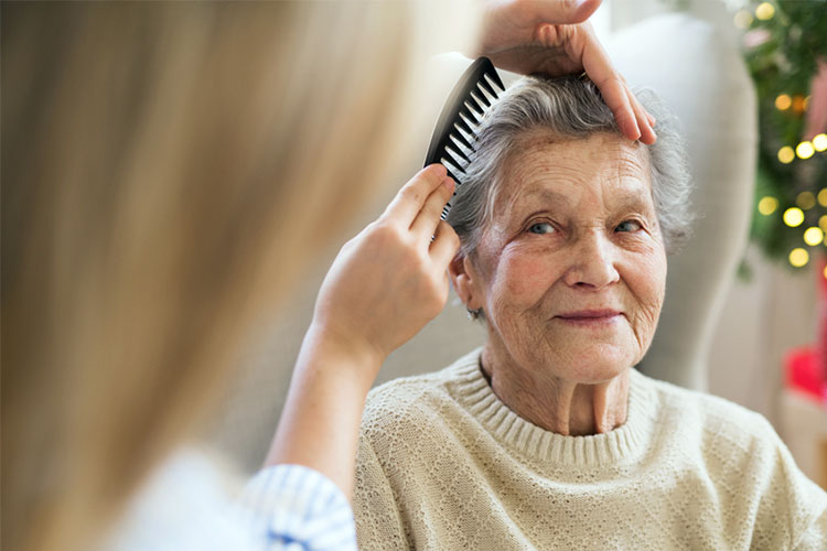 old woman with dementia has her hair combed for her by carer