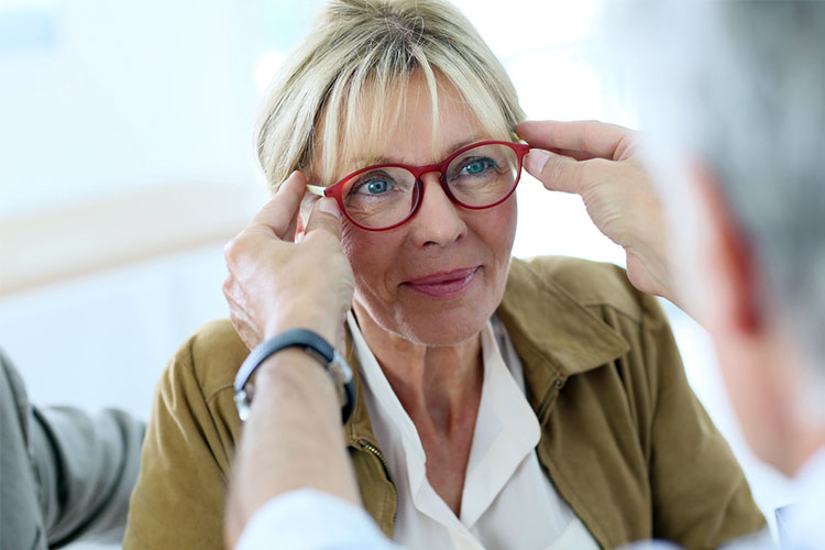 senior woman is having glasses fitted to help with visions loss or difficulties
