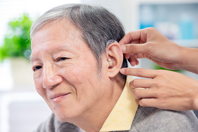 old man with deafness is having hearing aid fitted