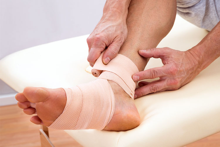 Person putting a bandage on their foot | Image
