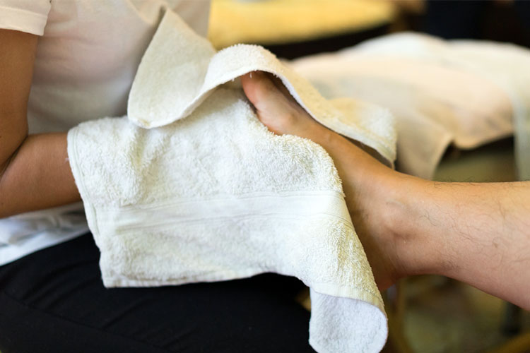 Healthcare workder drying a patients foot | Image