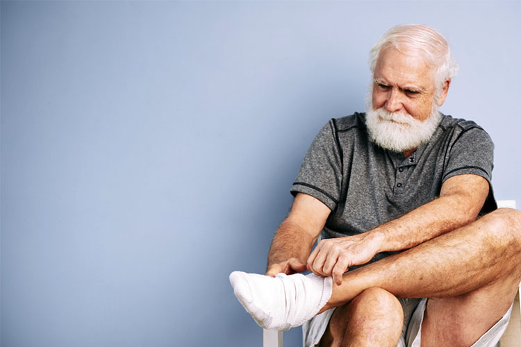 Elderly male putting socks on | Image