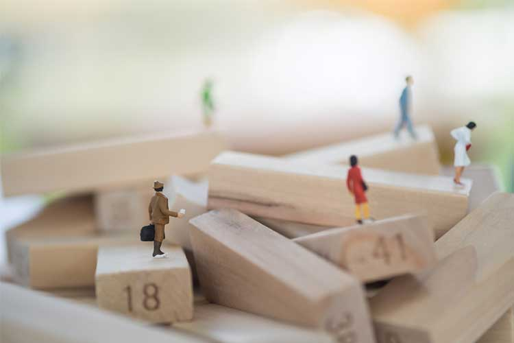 Human figurines on jenga blocks | Image