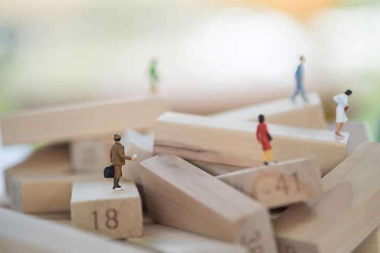 Human figurines on jenga blocks | Image