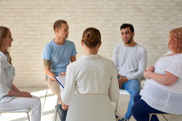 group therapy session of people seeking treatment for post-traumatic stress disorder