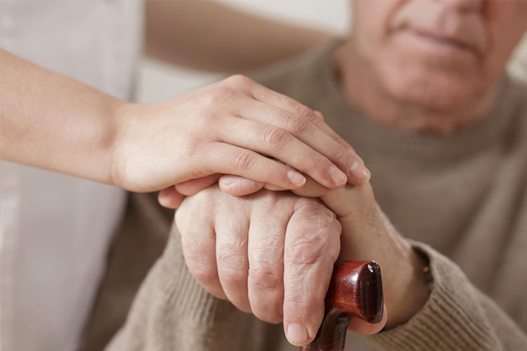 Carer holding elderly persons hand | Image