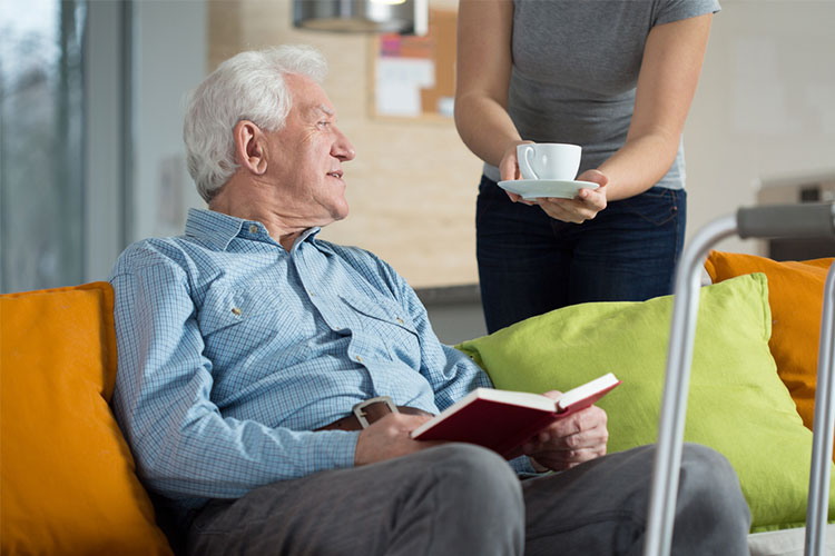 Elderly male being presented a hot beverage whilst reading | Image