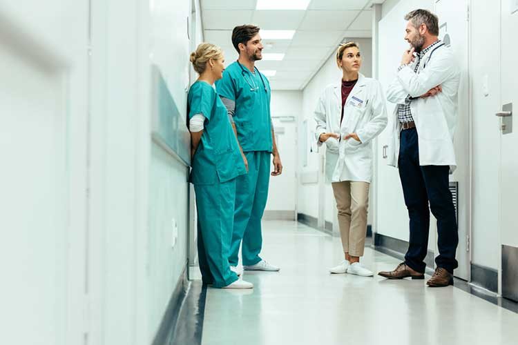 Healthcare professionals talking in hallway | Image