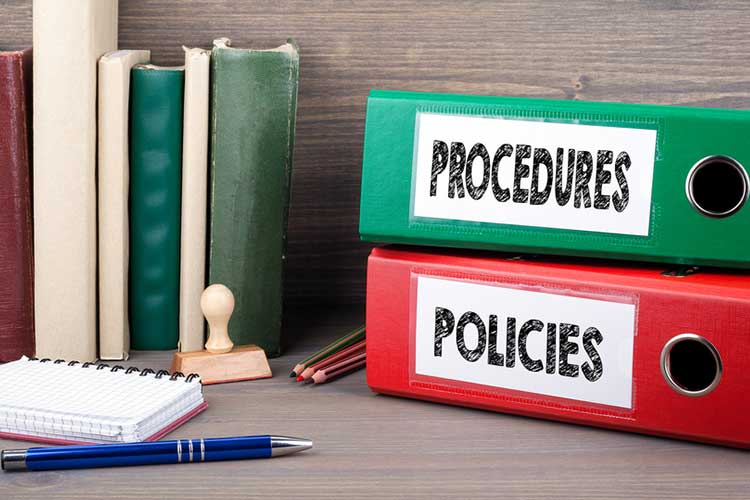 policies and procedures folders on a desk