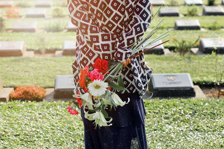 Woman at a cemetary holding flowers | Image