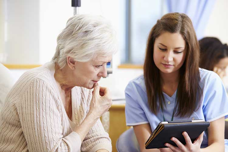 Nurse showing elderly person something on a tablets | Image