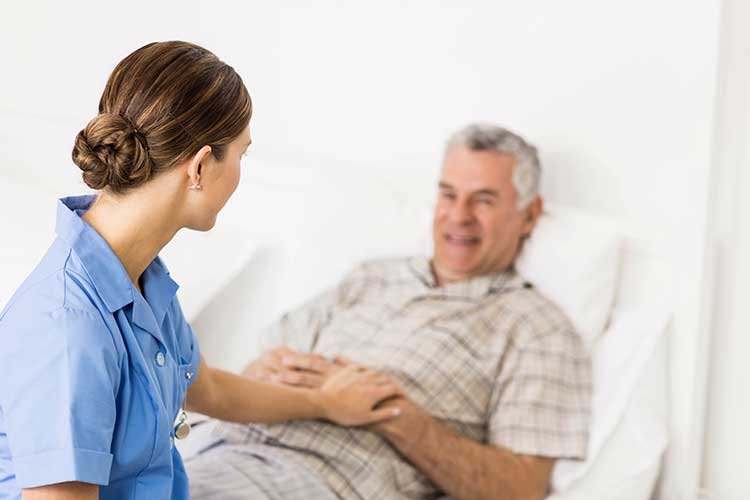 Nurse with elderly man in bed   Image