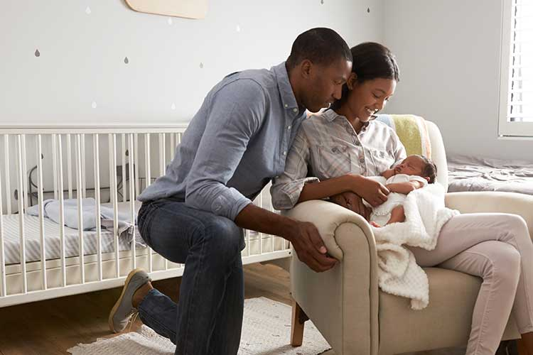 Young couple comforting baby in a nursery | Image
