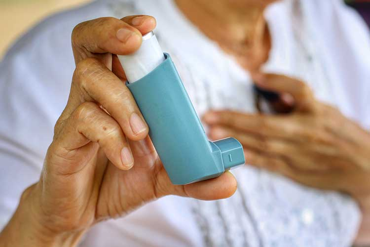 Elderly woman holding an asthma inhaler | Image