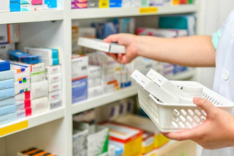 Pharmacist putting products on shelf | Image