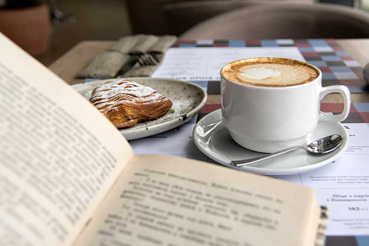 reading at cafe with a cup of coffee and pastry