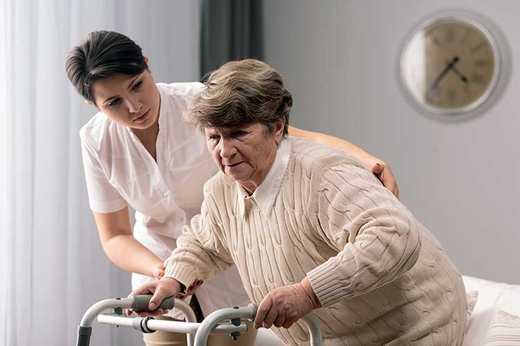 nurse helping older woman to stand up