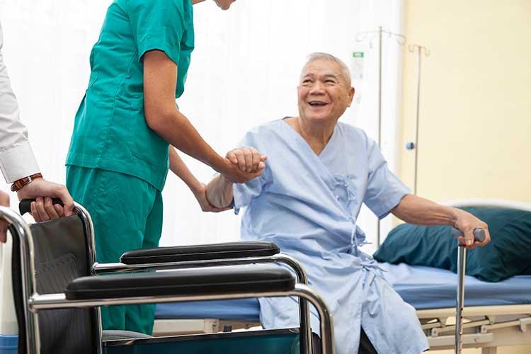 nurse helping older man get out of hospital bed