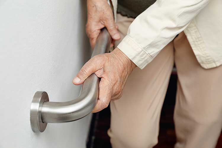 older adult holding handrail