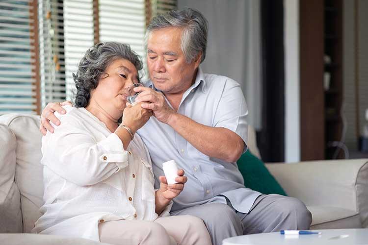 carer helping woman take medicine