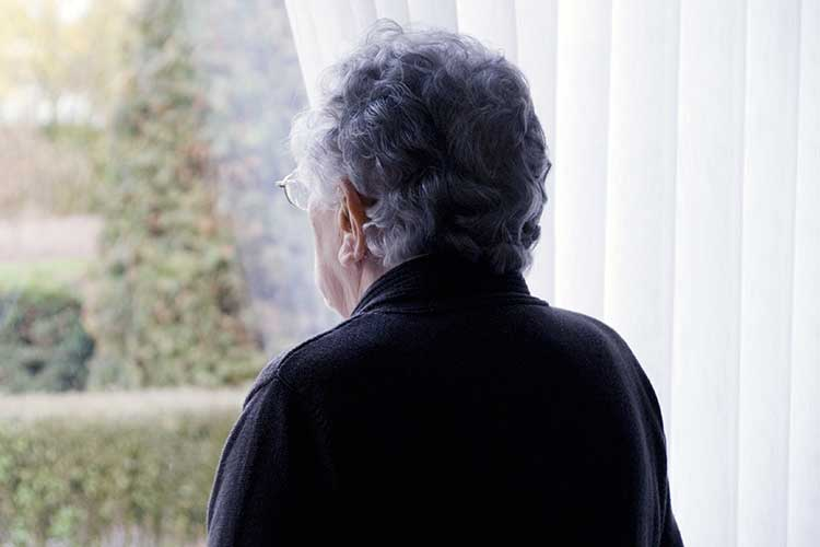 socially isolated woman looking out window