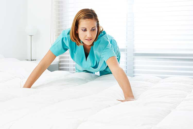 home care worker making bed