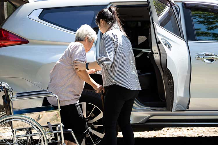 carer helping client get into car