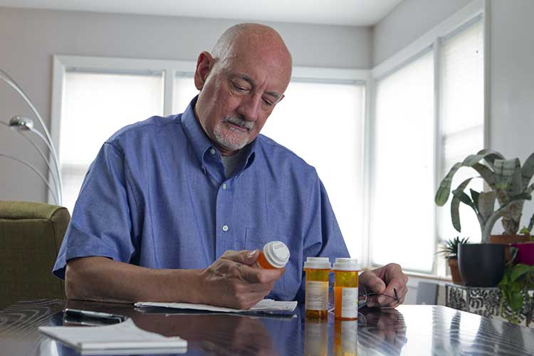 man checking medicine label for side effects